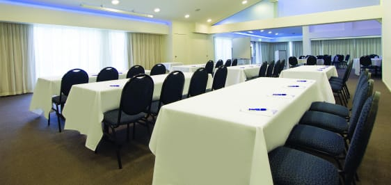 row of tables and chairs in front of projector in conference room for hire for events in Caloundra, Sunshine Coast