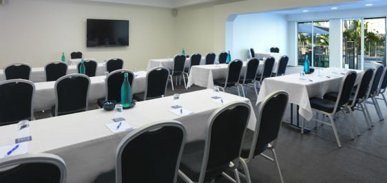 tables and chairs in functions room with tv and air conditioning at Oaks Oasis Resort hotel in Caloundra, Sunshine Coast