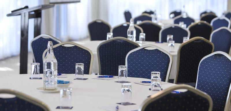 close up view of tables with pens and notepads and lectern in background in conference room for hire in Caloundra on Sunshine Coast QLD