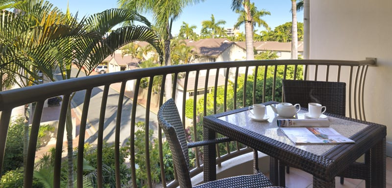 private balcony of 1 bedroom executive hotel apartment with coffee mugs on table and views of Oaks Oasis Resort in Caloundra on Sunshine Coast, Queensland, Australia