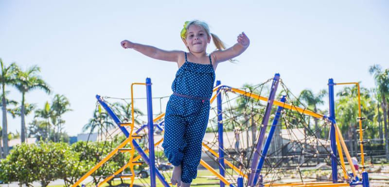 young girl having fun at Adventure Zone with jungle gym in background at Oaks Oasis Resort hotel on Sunshine Coast