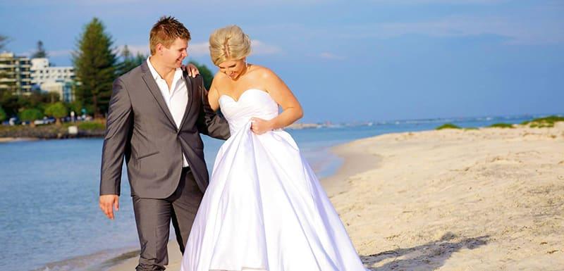 smiling bride and groom walking on beach in Caloundra on Sunshine Coast, Queensland, Australia