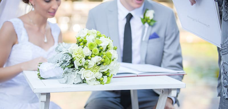 happy young married couple signing wedding certificate after ceremony