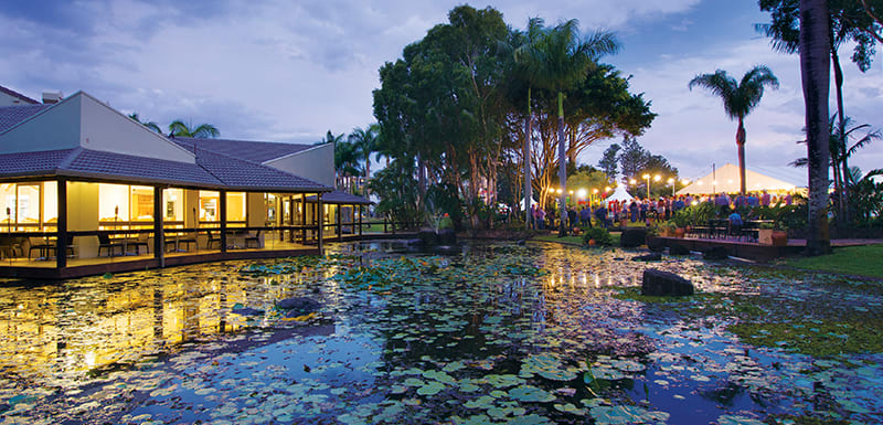 fishpond at dusk with sun setting over palm trees next to Reflections Restaurant and Bar best restaurant in Caloundra