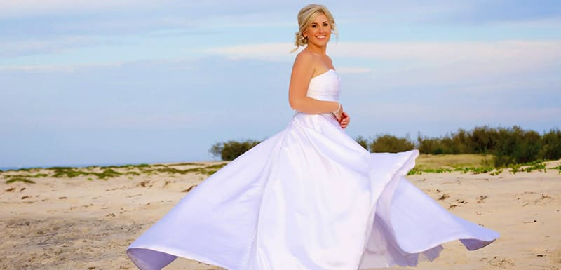 beautiful bride on beach with long white wedding dress at sunset in Caloundra, Queensland, Australia
