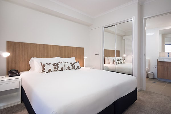 air conditioned bedroom queen size bed with clean sheets and full length mirror in one bedroom executive apartment at Oaks Rivermarque hotel in Mackay, Queensland, Australia