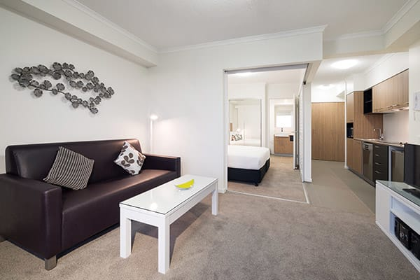 air conditioned apartment living room with leather couch, TV with Foxtel and kitchenette in one bedroom executive apartment at Oaks Rivermarque hotel in Mackay, Queensland, Australia