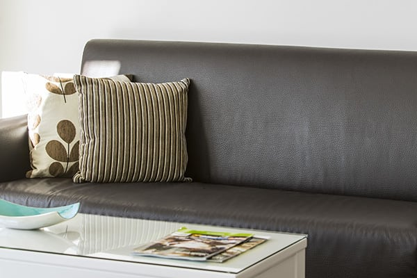 leather couch with comfortable pillows and table with magazines in one bedroom executive apartment at Oaks Rivermarque hotel in Mackay, Queensland, Australia
