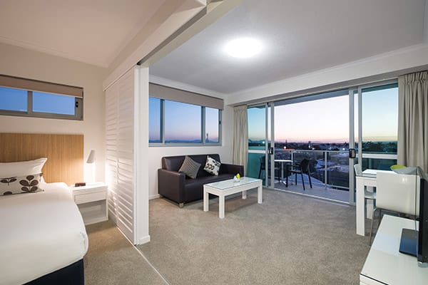 open plan apartment with queen size bed and living room with TV in one bedroom apartment at Oaks Rivermarque hotel in Mackay, Queensland, Australia