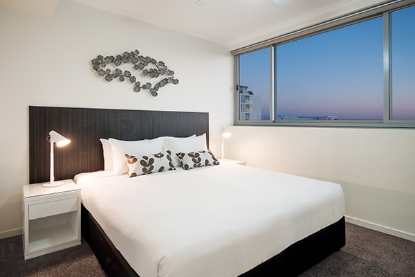 Hotels in Mackay with queen size bed in air conditioned master bedroom with big windows in two bedroom apartment at Oaks Rivermarque hotel, Queensland, Australia