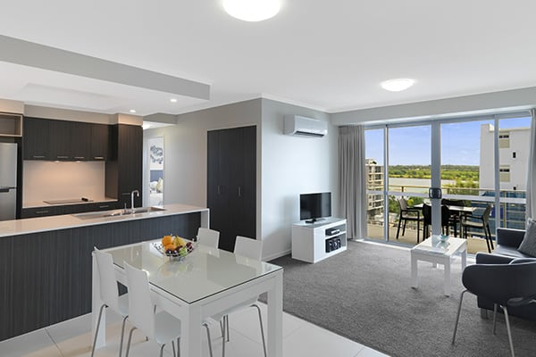 large living room with air conditioning, TV, dinner table, couches and private balcony in 2 bedroom apartment at Oaks Rivermarque hotel in Mackay, Queensland, Australia