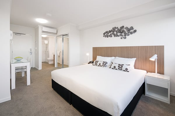 air conditioned bedroom with queen size bed and desk in hotel room apartment at Oaks Rivermarque in Mackay, Queensland, Australia