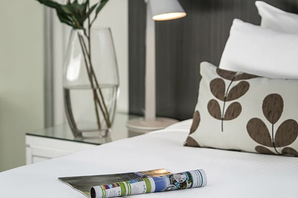 close-up of magazine and pillows on double bed in hotel room apartment at Oaks Rivermarque in Mackay, Queensland, Australia