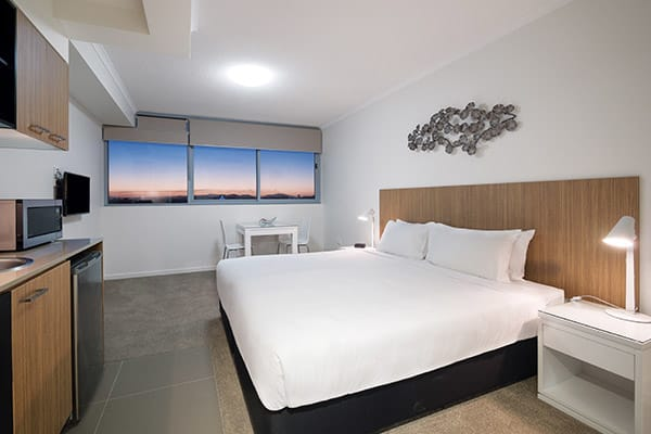 queen size bed in air conditioned bedroom of Studio room apartment with TV and Foxtel at Oaks Rivermarque hotel in Mackay, Queensland, Australia