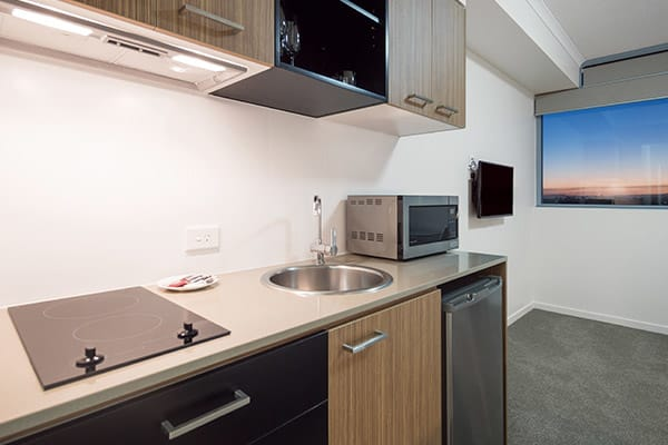 kitchen with microwave, fridge, oven, kettle, toaster and stove top in air conditioned Studio room apartment at Oaks Rivermarque hotel in Mackay, Queensland, Australia