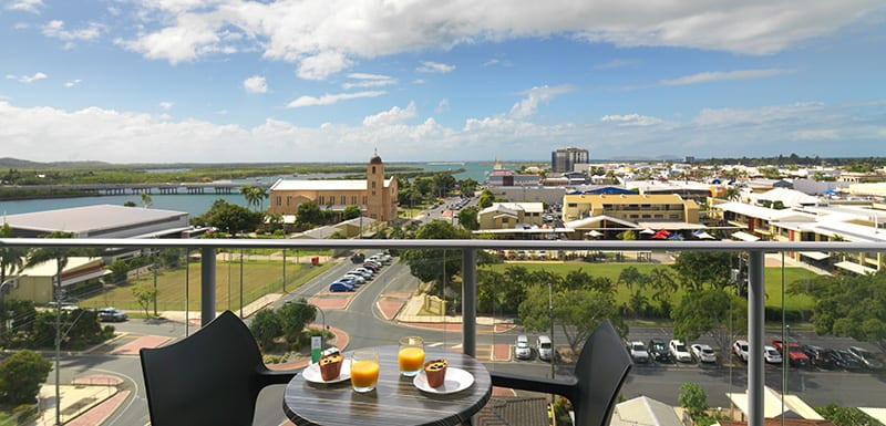 hotel accommodation Mackay with balcony, table and chairs and beautiful view of Mackay and Pioneer River at Oaks Rivermarque hotel