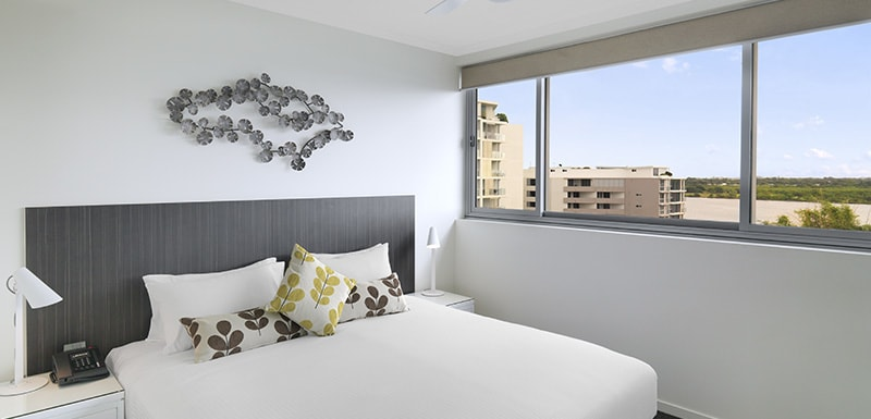 picture of queen size bed with clean sheets, lots of storage space and Wi-Fi for guests at Oaks Rivermarque hotel in Mackay, Queensland, Australia