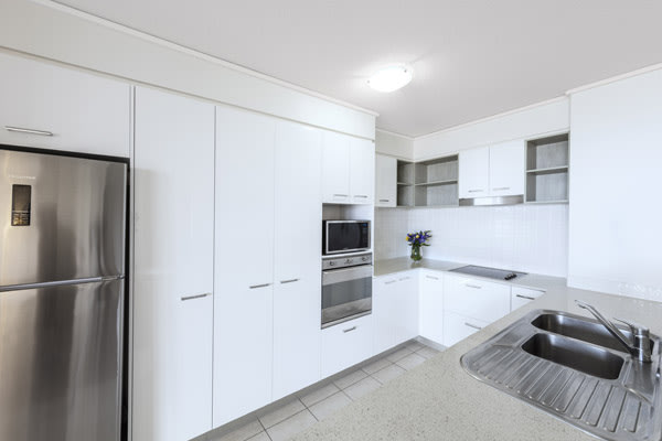 kitchen with microwave, large refrigerator, kettle and stove in 2 bedroom apartment at Oaks Seaforth Resort hotel, Sunshine Coast