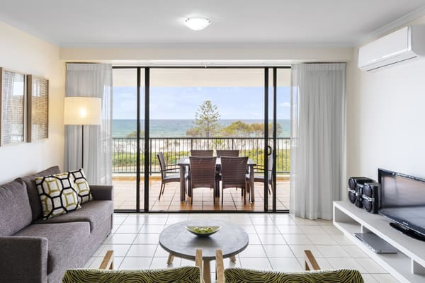 air conditioned 2 bedroom apartment living room with furniture and private balcony with tables and chairs and views of ocean at Oaks Seaforth Resort hotel, Sunshine Coast