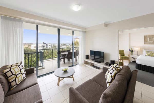 spacious air conditioned living room with TV with Foxtel and private balcony with ocean views in 3 bedroom apartment near beach at Oaks Seaforth Resort hotel, Sunshine Coast, Queensland, Australia