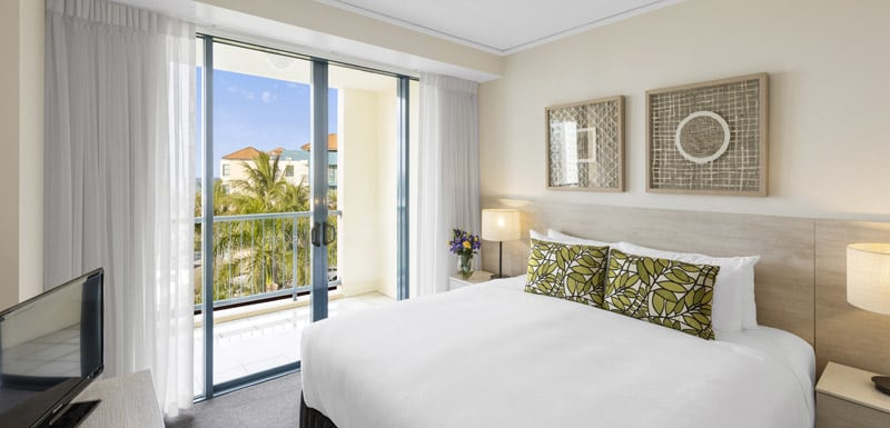queen size bed in air conditioned 2 bedroom ocean view apartment near beach with private balcony and Foxtel on television at Oaks Seaforth Resort hotel, Sunshine Coast, Queensland, Australia