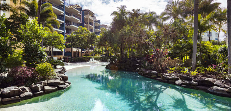 lagoon pool lined with palm tress at Oaks Seaforth Resort hotel in summer perfect for families on holiday on the Sunshine Coast, Queensland, Australia