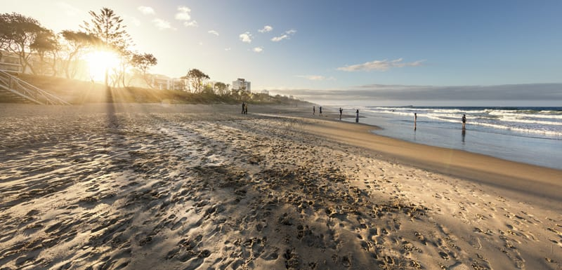 tourists on Maroochydore beach at sunrise near Oaks Seaforth Resort hotel, Sunshine Coast, Queensland, Australia