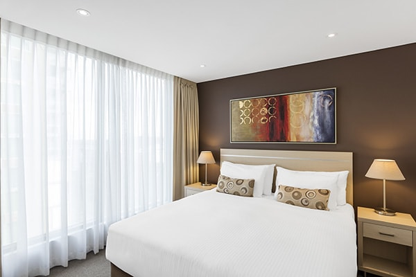 large queen size bed in big 1 bedroom hotel apartment accommodation in Adelaide CBD