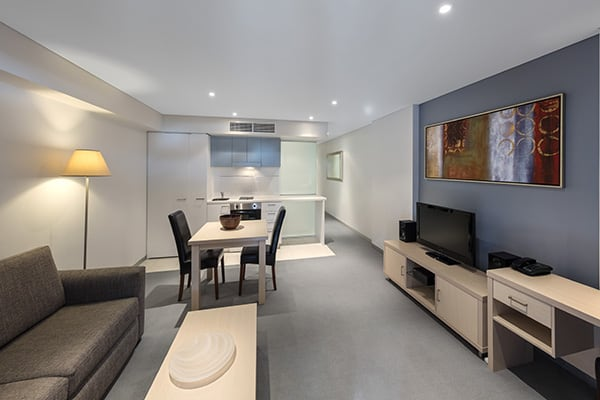 open plan living room with Foxtel on TV, air conditioning, tables, chairs and kitchenette in Adelaide city
