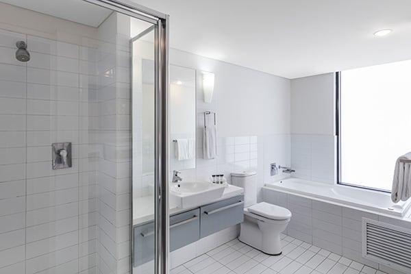 2 bedroom apartments en suite bathroom with bath tub, shower, toilet, mirror and clean towels