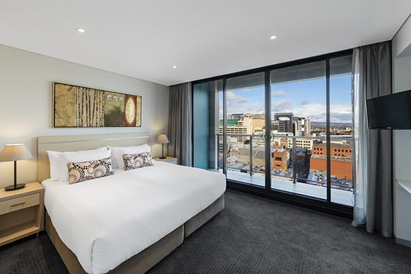air conditioned bedroom walking distance to the Adelaide Oval with Wi-Fi, private balcony, big bed and satellite TV