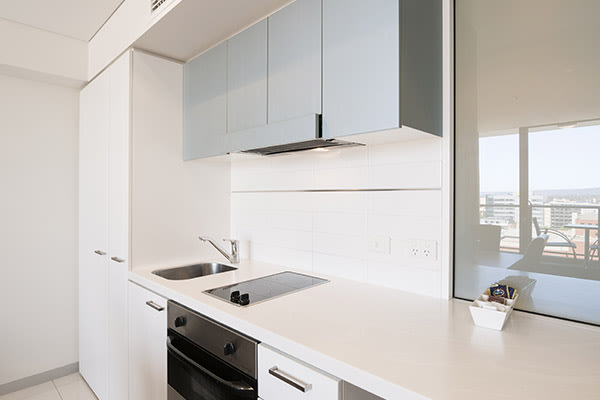 2 bedroom apartment kitchen with large refrigerator, storage cupboards, oven, microwave, kettle, toaster and dishwasher