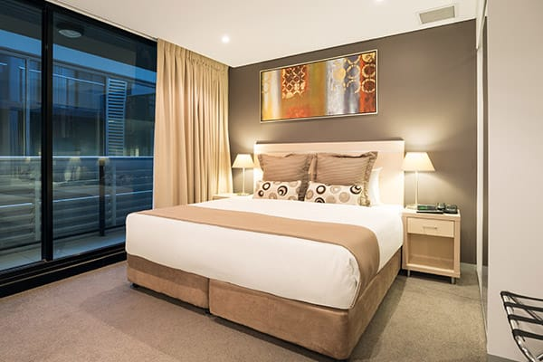 interior view of air conditioned 2 bedroom apartment at Oaks Horizons hotel near Adelaide Oval with queen size bed and private balcony outside