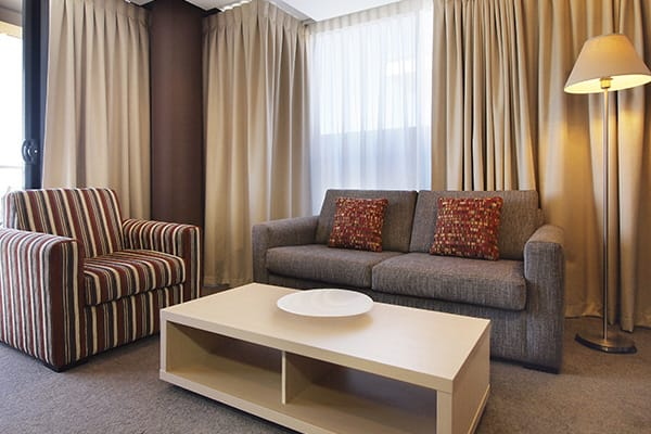 table and couches in living room of 2 bedroom apartment walking distance from Adelaide Oval cricket and AFL ground