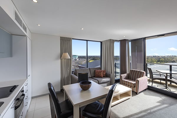 dining room table with chairs next to kitchenette in 2 bedroom apartment with air conditioning at Oaks Horizons hotel near Adelaide Oval