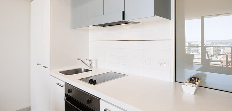 kitchenette in 2 bedroom apartment with stove top hot plates, oven, kettle, microwave, toaster and refrigerator