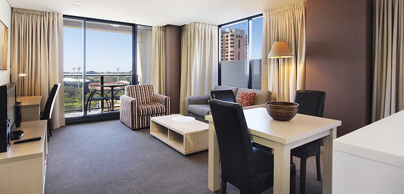 2 bedroom apartment living room with wi-fi, modern furniture, satellite TV and private balcony with view of Adelaide Oval cricket and AFL stadium across the river