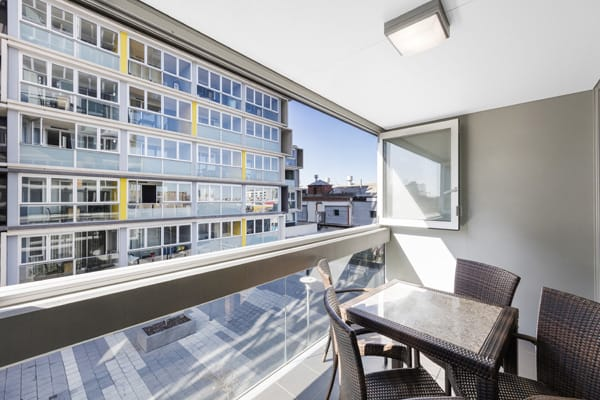 large balcony with table, chairs and views of Adelaide city outside 1 bedroom apartment at iStay Precinct hotel