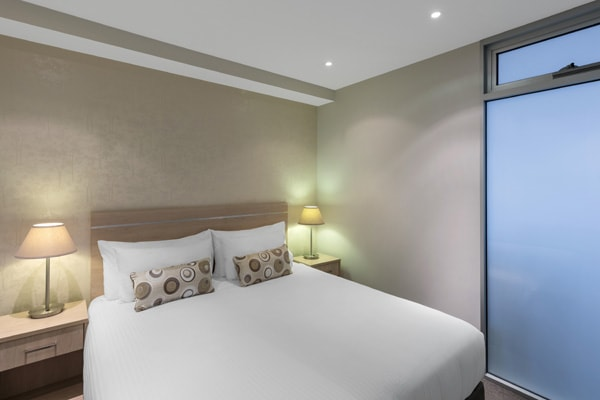 queen size bed and large windows in air conditioned 1 bedroom apartment near Adelaide Zoo in South Australia