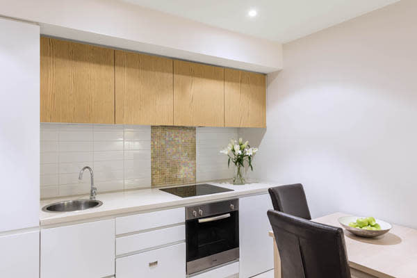 kitchen area with microwave, oven, fridge, freezer and dining table with chairs in 2 bedroom apartment at iStay Precinct hotel in Adelaide city