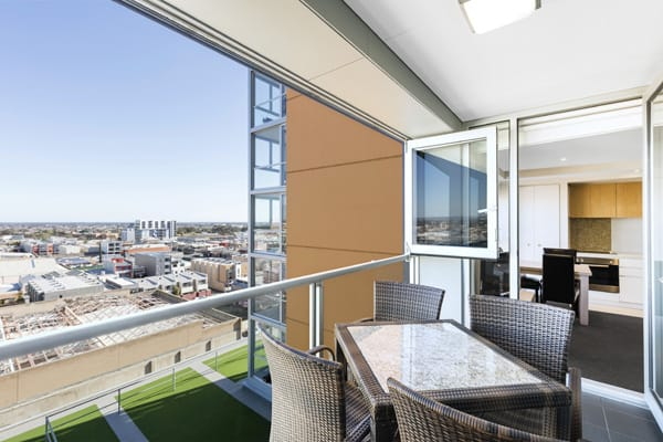 private balcony with table and chairs outside 2 bedroom air conditioned apartment at iStay Precinct hotel in Adelaide city