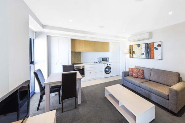 large living room with couches, TV with Foxtel and kitchen in background with microwave, kettle and toaster in Adelaide 2 bedroom hotel apartment