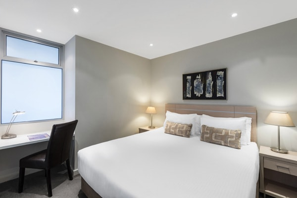 master bedroom of 2 bedroom apartment with chair and desk for corporate travellers to do work while visiting Adelaide on business