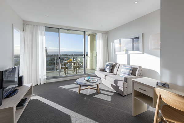 Best Glenelg hotels with large living room with Foxtel on TV, big, comfortable couches and private balcony outside with views of Glenelg and the ocean