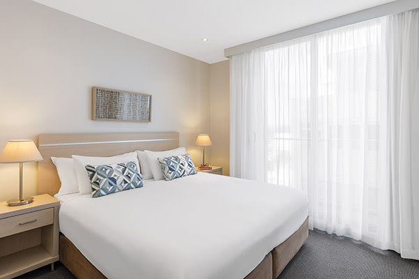large bed with clean sheets and big pillows in air conditioned 2 bedroom apartment at Oaks Liberty Towers hotel in Glenelg, South Australia