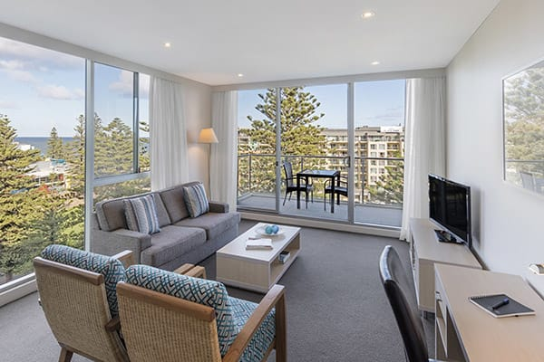 large air conditioned living room with Foxtel on TV and private balcony outside with views of sea and beach at Oaks Liberty Towers hotel in Glenelg, South Australia
