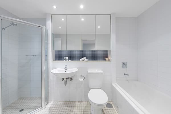 clean en suite bathroom with toilet, shower and bath tub in 3 bedroom apartment at Oaks Liberty Towers hotel in Glenelg, South Australia