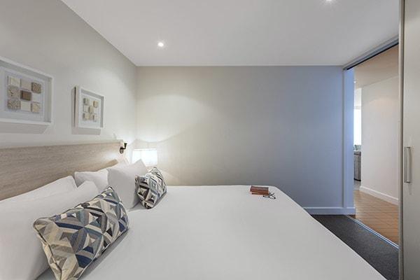fluffy pillows on queen size bed with clean sheets in air conditioned 3 bedroom apartment with Wi-Fi near the ocean in Glenelg, South Australia