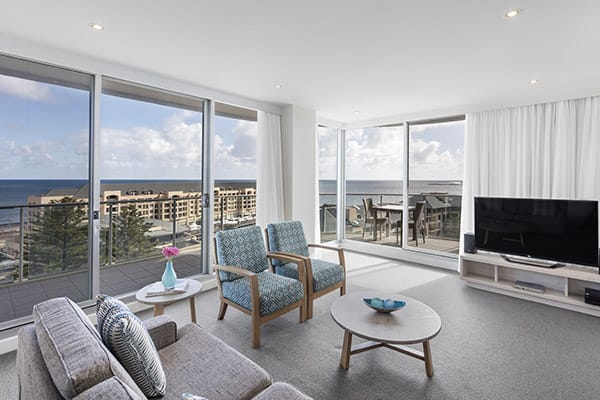 large air conditioned living room with big flat screen TV and private balcony with ocean views at Oaks Liberty Towers hotel 3 bedroom apartment in Glenelg, South Australia