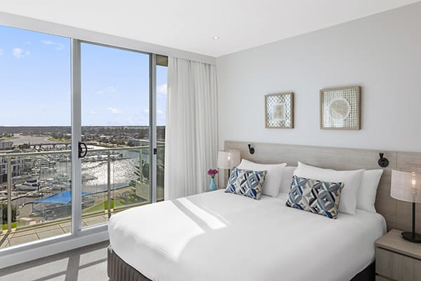 Interior of air conditioned Glenelg hotels master bedroom with large king size bed and sliding glass windows leading to private balcony with views of ocean at Oaks Liberty Towers hotel in Glenelg, South Australia